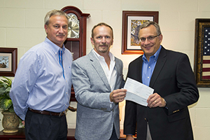 ExxonMobil handing donation check to Dr. Greg Poole